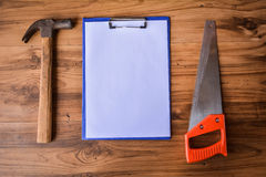 Saw with hammer and Clipboard on wood. Stock Images