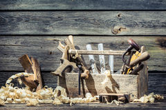 Saw, hammer and planer in the carpentry workshop. On old wooden table Stock Photography