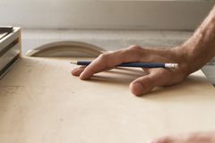 Saw. Hand of a worker while cutting with circular saw royalty free stock photography