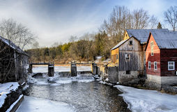Old Mill. Saw Mill and river dam in winter Stock Image