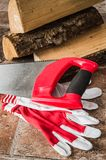 Saw, mittens and firewood, close-up royalty free stock photos