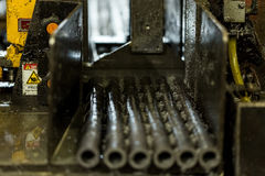 Saw. Steel bushes are cut on the bench saw. Procurement in bulk. Stock Photos