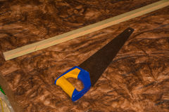 Saw with thermal insulation wool royalty free stock photography