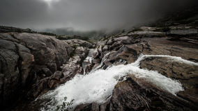 Dark clouds and a rough waterfall. Saw this waterfall during a walk in Norway Stock Images