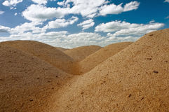 Sawdust. Dunes of sawdust against the cloudy sky stock images