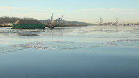 Sawdust Barge and Tugboat on Icy Fraser River. A tug boat towing a barge down the icy Fraser River in winter near Vancouver. British Columbia, Canada stock video