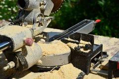 Sawdust on circular saw outdoors. A Sawdust on the circular saw outdoors Royalty Free Stock Photography