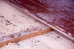 Sawdust insulation under old floor boards. Sawdust insulation under floor boards show some depression (sagging) over time Royalty Free Stock Photo