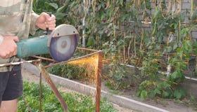 Sawing de Metal de la amoladora de ángulo con las chispas que destellan cerca para arriba foto de archivo