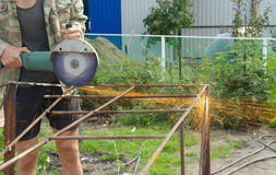 Sawing de Metal de la amoladora de ángulo con las chispas que destellan cerca para arriba fotos de archivo