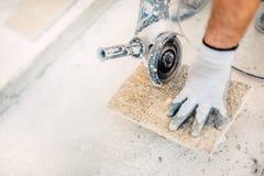 Sawing de piedra del trabajador, funcionamiento con las herramientas eléctricas en emplazamiento de la obra fotografía de archivo