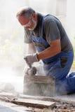 Sawing dell'uomo con la smerigliatrice Fotografia Stock