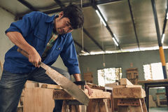 Sawing man. Asian carpenter sawing a wooden plank in workshop Royalty Free Stock Image
