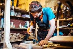 Sawing. Modern handyman sawing wooden board in his workshop Stock Photos