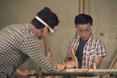 Sawing plank for the first time. Asian mature men explaining his teen son how to saw wooden planks Stock Photos