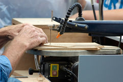Sawing wood. Man sawing wood on a machine Stock Image