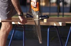 Sawing Wood. Carpenter sawing wood Stock Image