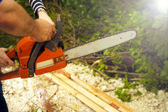 Sawing wood with a chainsaw. Carpenter working Stock Photo