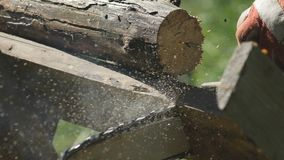 Sawing a wooden plank with a chainsaw, the gardener`s hands hold the saw and saws the firewood for home use, side view stock footage