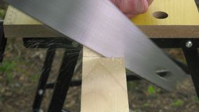 Sawing a wooden square with a wood saw. The square wood is firmly lock in the workbench stock video