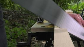 Sawing a wooden square with a wood saw. The square wood is moved in the workbench stock footage