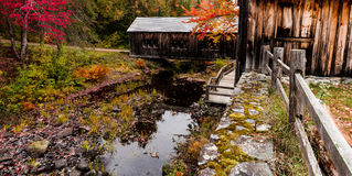 Sawmill antique. Leonards Mill Maine fall autumn colors old fashioned leaves chill orange red yellow season saw wood covered bridge Stock Image