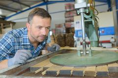 Sawmill employee working with wood tools and machinery. Sawmill royalty free stock photography