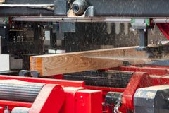 sawmill Processen av att bearbeta med maskin loggar in utrustnings?gverkmaskinen s?g att s?gar tr?dstammen p? plankan stiger ombo arkivfoton