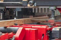 sawmill Processen av att bearbeta med maskin loggar in utrustnings?gverkmaskinen s?g att s?gar tr?dstammen p? plankan stiger ombo royaltyfria foton