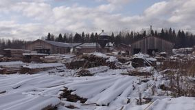 Sawmill yard stored piles of lumber materials covered in snow. On cloudy winter day stock footage