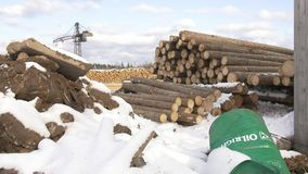 Sawmill yard stored piles of lumber tree materials covered in snow. On cloudy winter day stock video footage