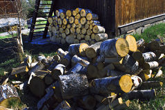 Sawn wood in front of house. Pile of sawn fire wood on background a woodpile near the house Royalty Free Stock Images
