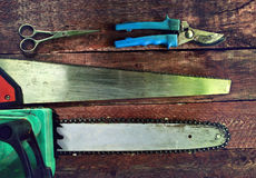 Saws and secateurs. Garden tools on a wooden background. Saws and secateurs Stock Images