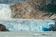 Sawyer Glacier. A blue glacier flowing down a mountainside into the ocean Royalty Free Stock Photos