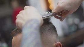 Saxen klippte huvudet av en grabb i mäns en hårsalong Manlig frisör som ansar män Frisyr och frisyr Trollkarlen arkivfilmer
