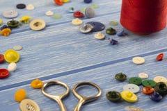 Saxen, knappar och trådar på en träbakgrund scissor royaltyfri fotografi