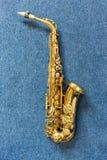 Saxofón de Golden del músico de jazz en la pared azul fotografía de archivo