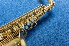 Saxofón de Golden del músico de jazz en la pared azul fotos de archivo