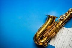 Saxofón de oro con la hoja de música Imagenes de archivo