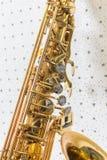 Saxofón de oro en el fondo blanco y azul de la pared imagenes de archivo