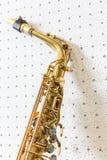 Saxofón de oro en el fondo blanco y azul de la pared foto de archivo