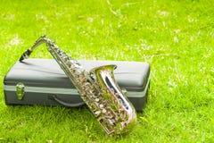 Saxofón de oro hermoso que miente a través de caja instumental negra en superficie herbosa Fotos de archivo libres de regalías
