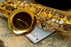 Saxofón junto con notas Imágenes de archivo libres de regalías