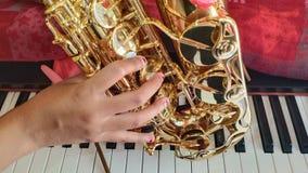 Saxofón, mano de la muchacha y el piano imagen de archivo