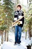 Saxofón que juega adolescente en la nieve Foto de archivo libre de regalías