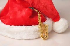Saxofón y casquillo rojo del ` s del Año Nuevo de Santa Claus Fotografía de archivo