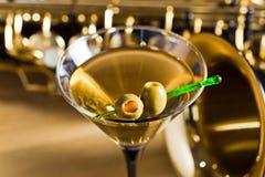 Saxofón y martini con las aceitunas verdes imágenes de archivo libres de regalías