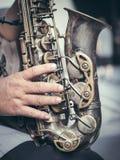 Saxofon i händerna Arkivbild