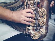 Saxofon i händerna på den stads- gatan Royaltyfri Foto