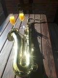 Saxofon med champagneexponeringsglas royaltyfri fotografi